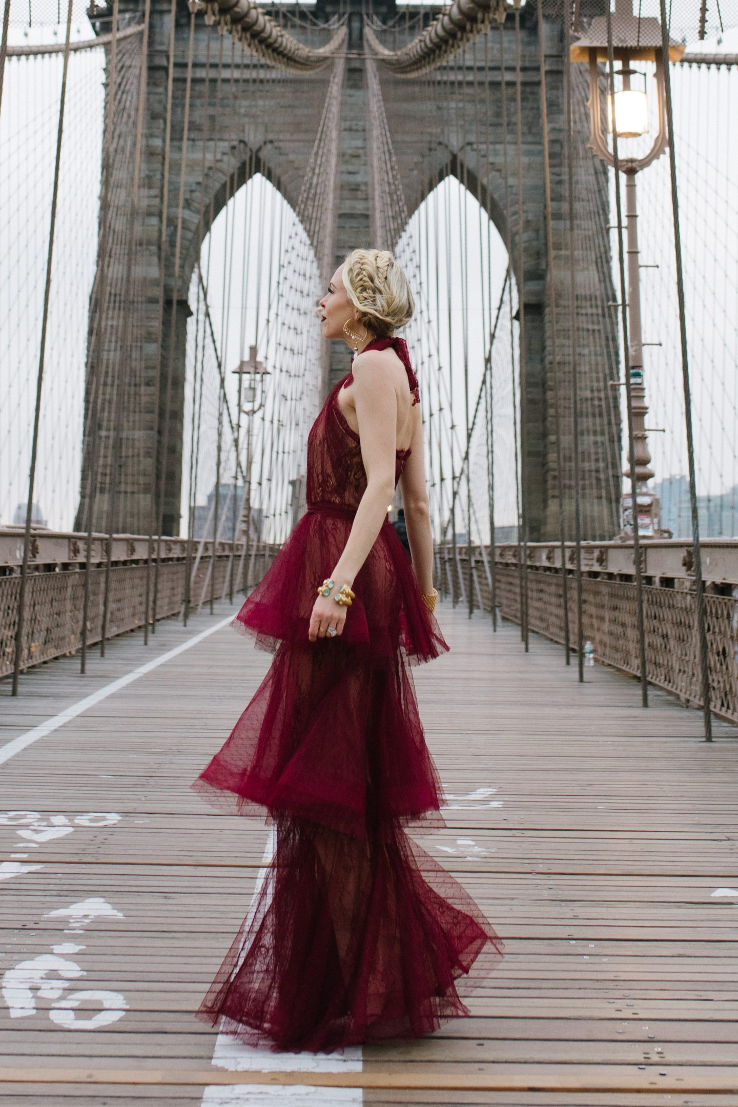 Redefining career success featured by top US life and style blog, Lombard and Fifth: image of a professional woman wearing a VICI dress, BHLDN earrings, Julie Vos cuff bracelets and standing on Brooklyn Bridge