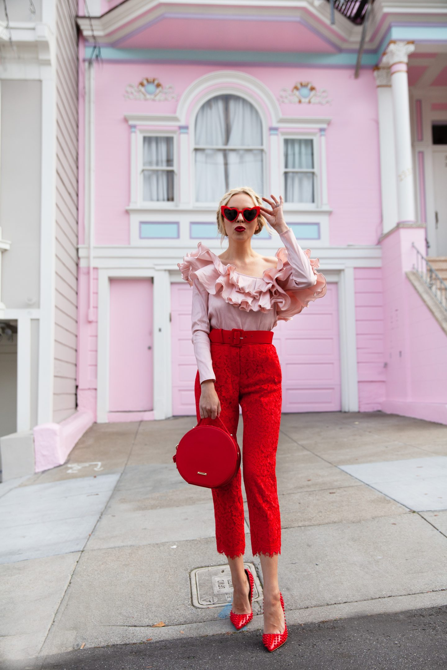 Valentines Day self care featured by top US life and style blog, Lombard and Fifth: image of a blonde woman wearing DressLily heart sunglasses, Roy Rogers red pants, a pink one shoulder ruffle blouse, Michka jeweled red pumps