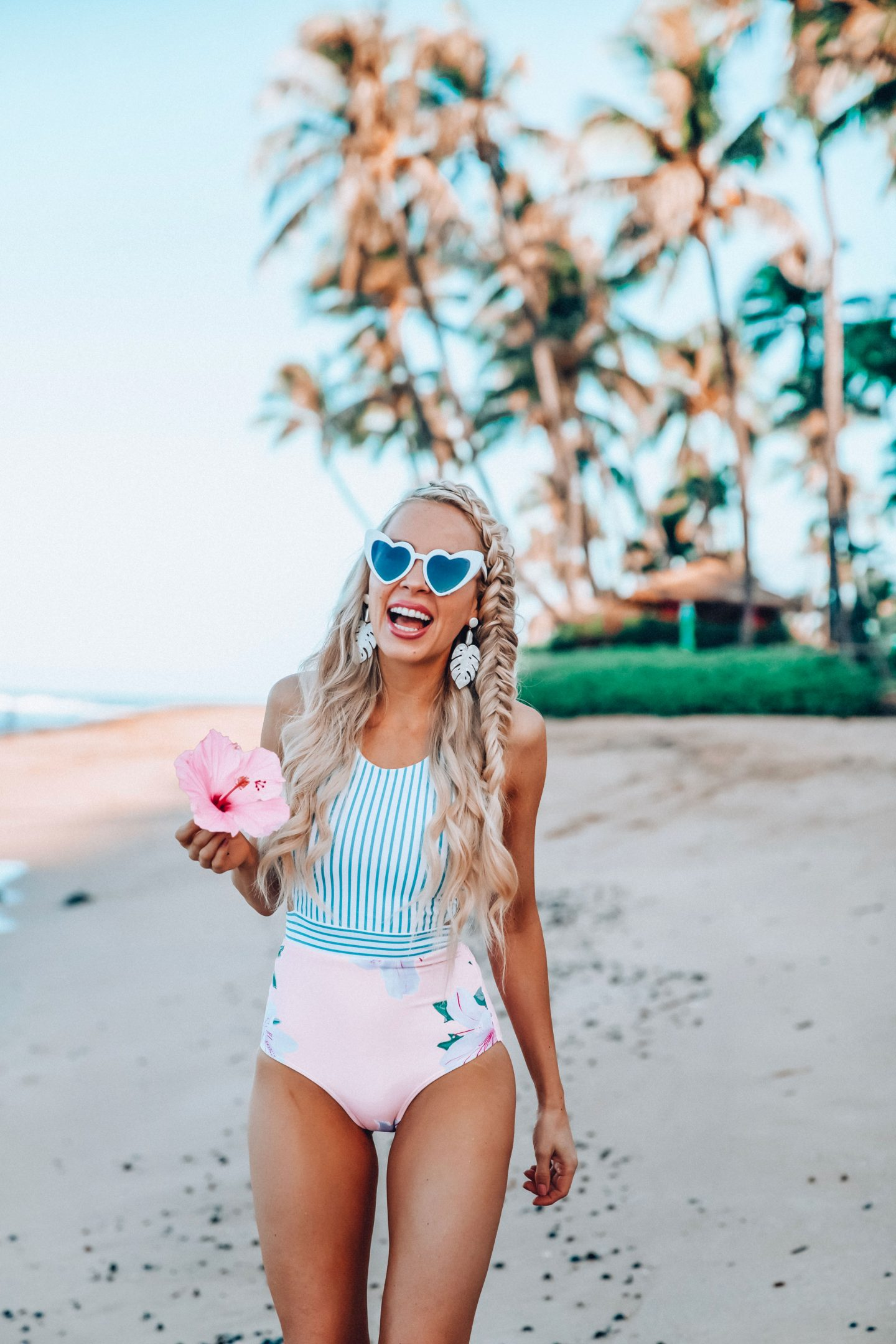 Swimwear Trends for Summer featured by top US fashion blog, Lombard and Fifth: image of a woman wearing an ALBION one piece floral swimsuit and silver heart sunglasses