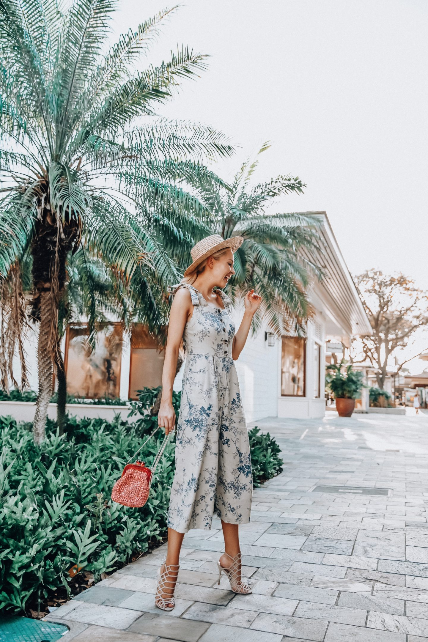 Gal Meet Glam collection favorites featured by top US fashion blog, Lombard & Fifth: image of a woman wearing a Gal Meet Glam floral jumpsuit, Aranaz beaded bag, Nordstrom Rack leather sandals, and Free People straw boater hat