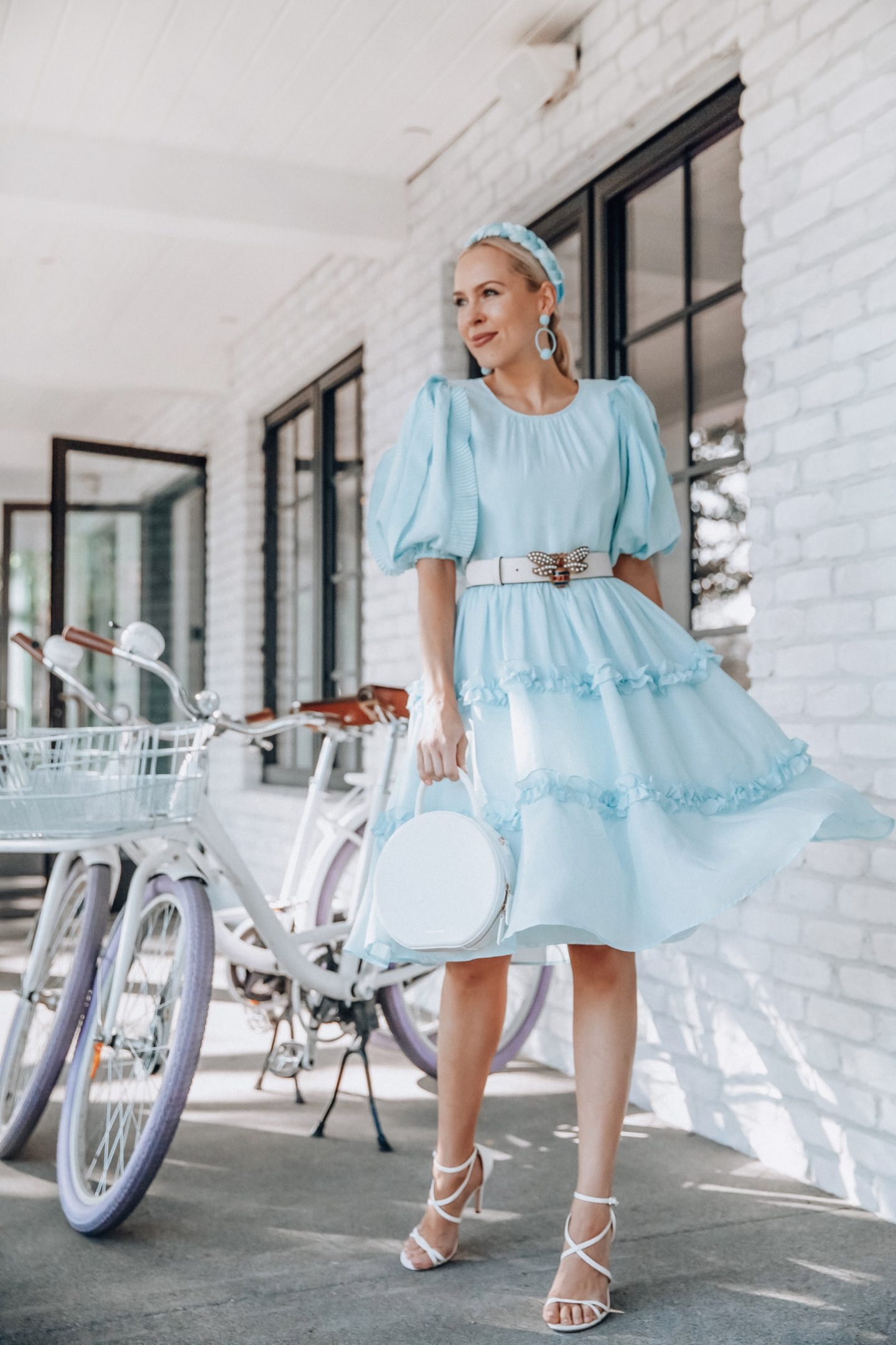 Baby blue fashion featured by top US fashion blog, Lombard and Fifth: image of a blonde woman wearing baby blue velvet headband, Rachel Parcell baby blue ruffle sleeve dress, Kendra Scott drop earrings, Gucci bee leather belt, and Mansur Gavriel white crossbody bag