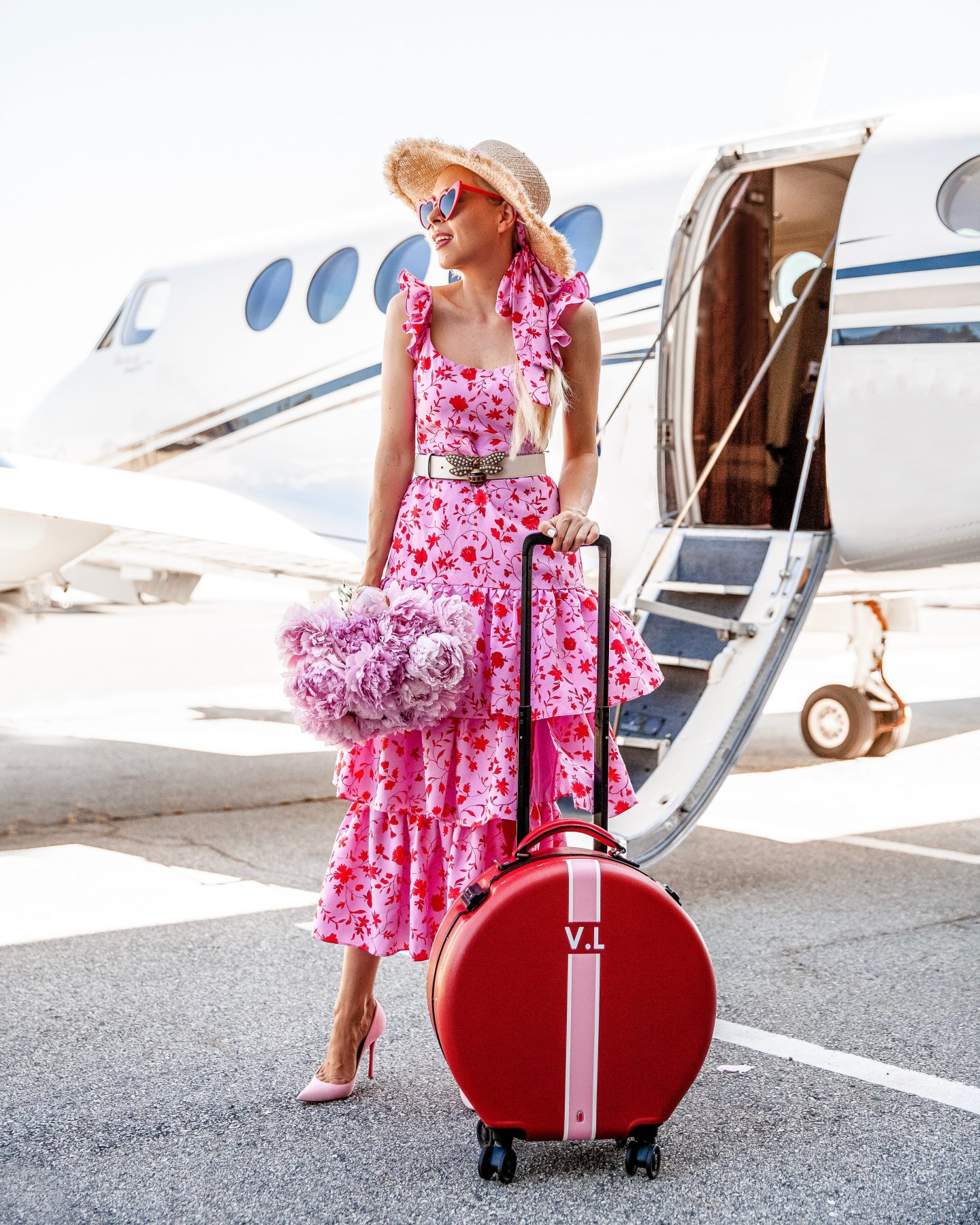 Best Personalized Brands featured by top US fashion blog, Lombard and Fifth: image of a woman wearing a Gucci queen bee leather belt, Aqua floral tiered maxi dress, Sam Edelman pointy pumps, and an ASOS straw hat, with a The Daily Edited monogrammed carry on suitcase